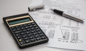 Calculator and pen on top of a monthly payroll sheet