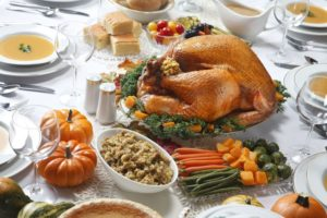 Thanksgiving dinner tablescape with a full turkey, stuffing, and side dishes.