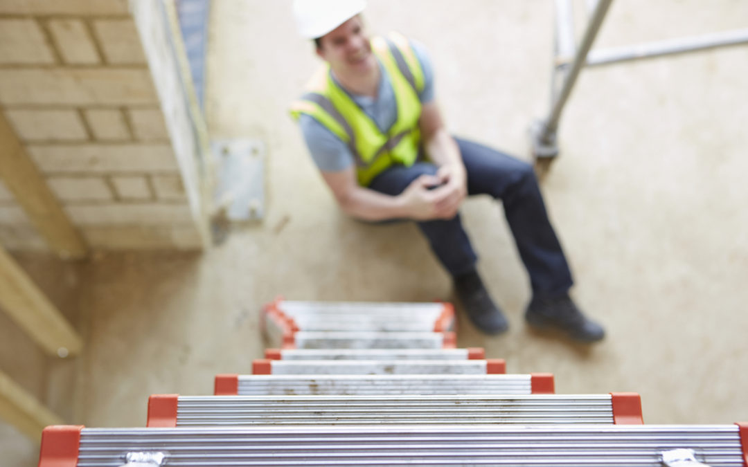 Construction worker in pain on the ground who definitely should have workers compensation coverage