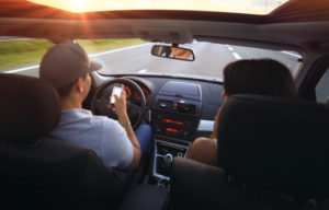 Two people in car with driver looking at phone